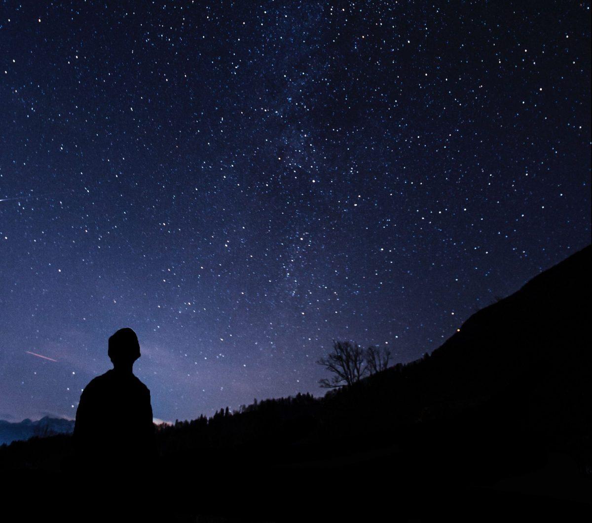 un homme regarde un ciel étoilé