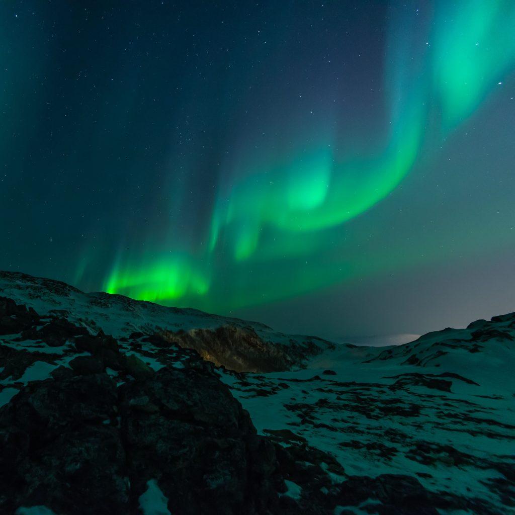 Aurore boréale verte sur un ciel nocturne bleu et montagne couverte de neige