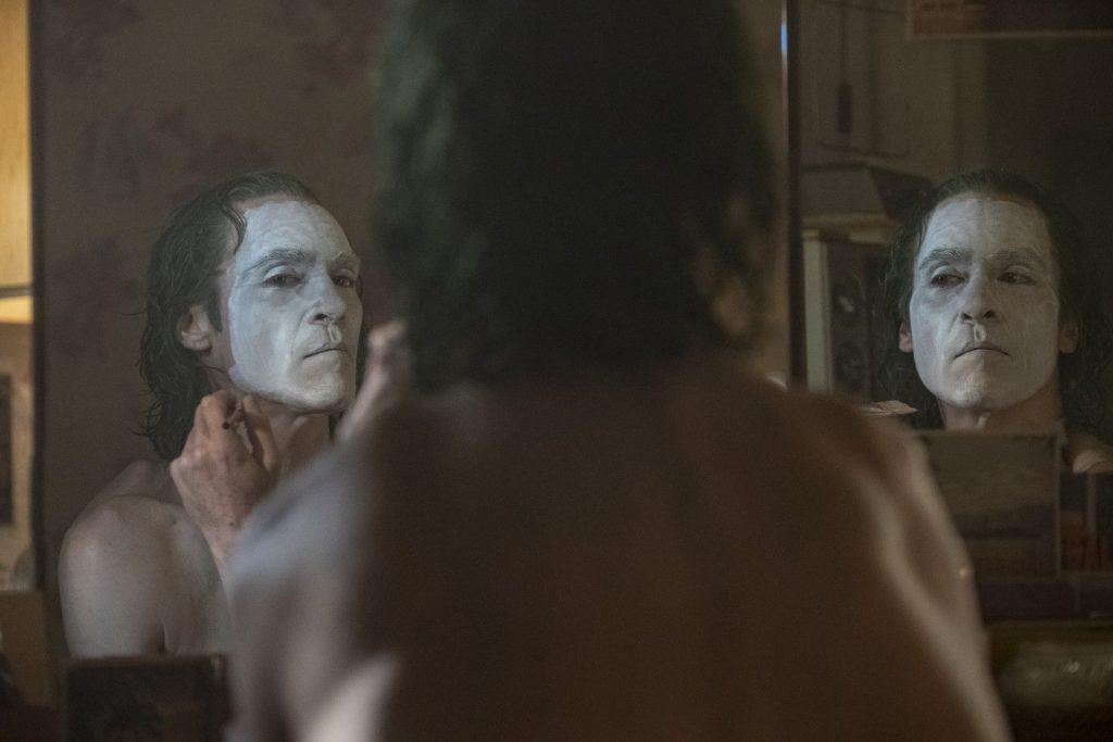 Arthur se maquille pour show. Il est très calme. Son miroir reflète son visage deux fois pour signifier sa folie.
