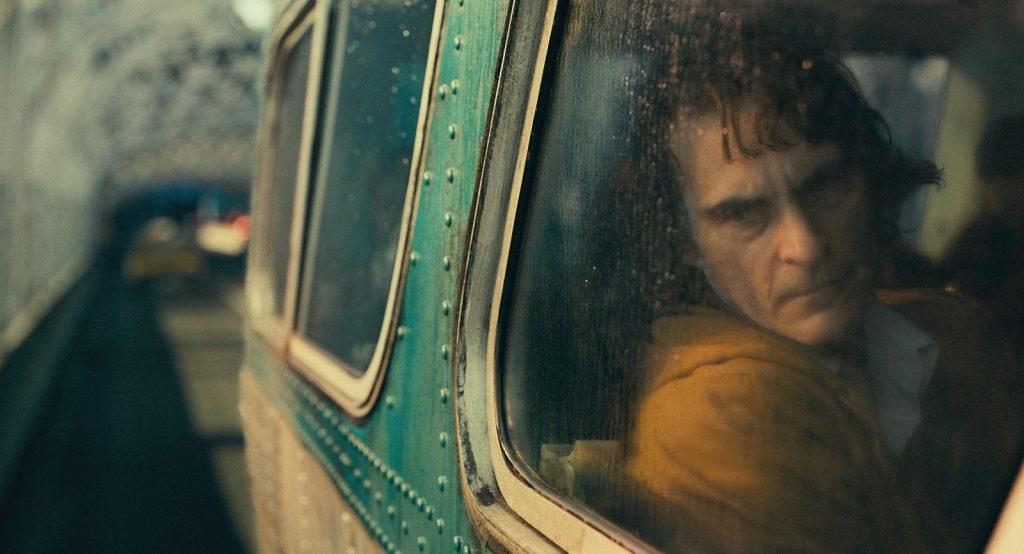 Arthur est dans le train. Il regarde dehors sur son trajet quotidien. Son air est morose.
