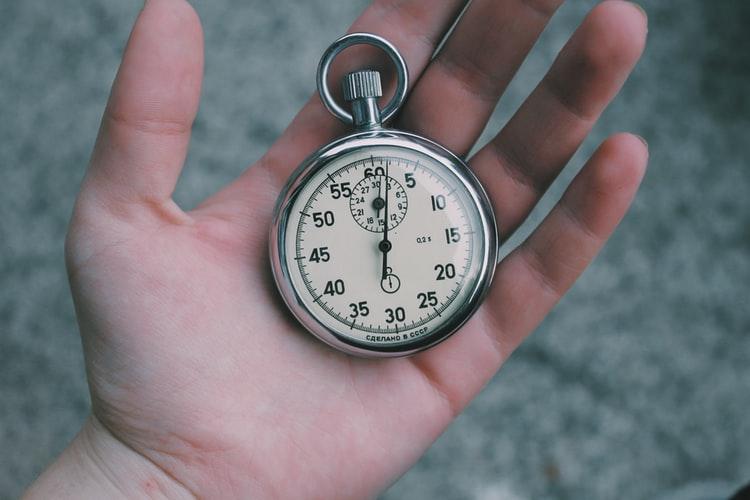 Une main tient un chronomètre de course