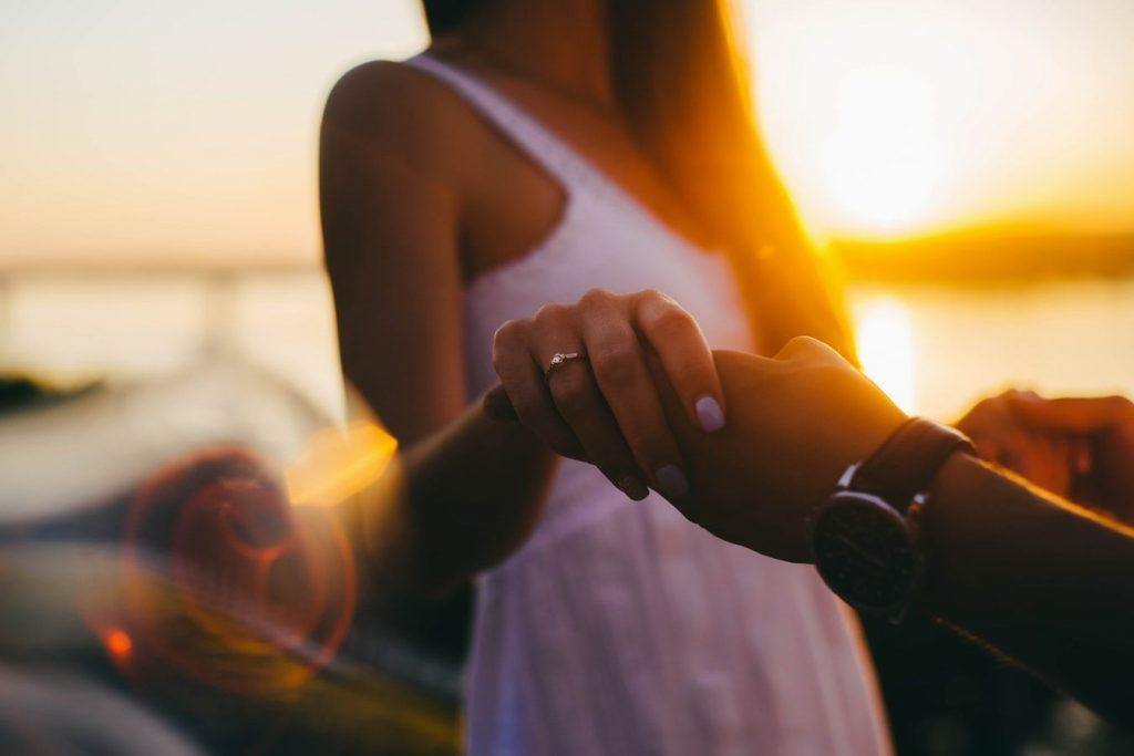 Un couple sous un coucher de soleil qui se tient la main.