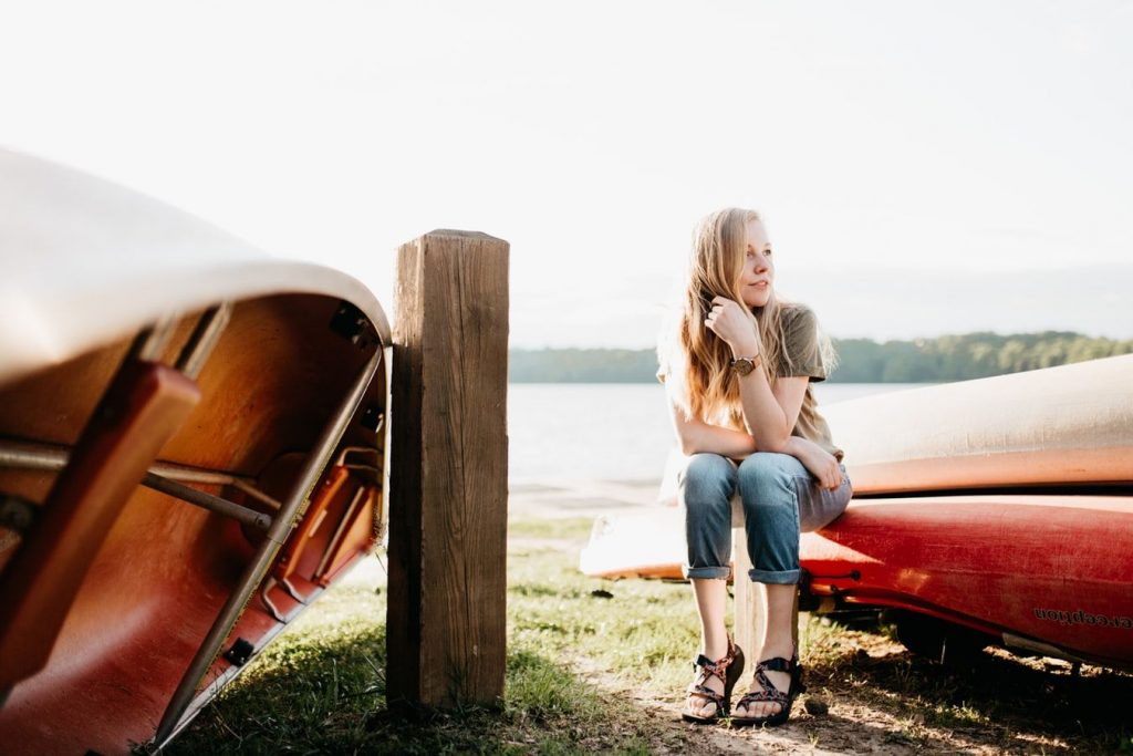 Une jeune femme est assise sur une barque, son regard est pensif mais elle sourit avec quiétude.