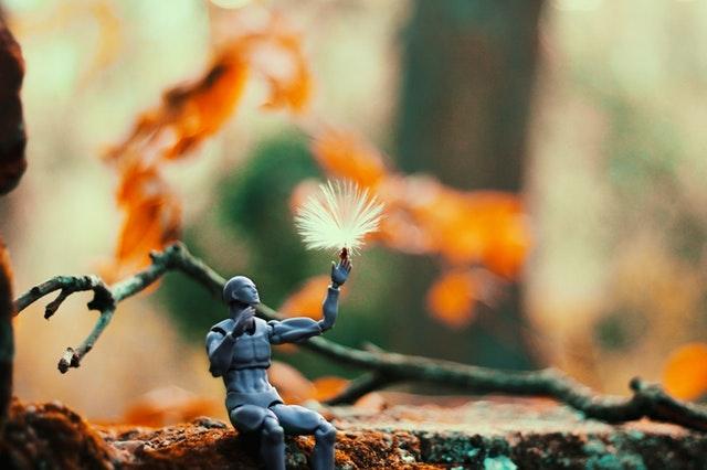 Figurine plastique assise sur une branche avec une fleur de pissenlit