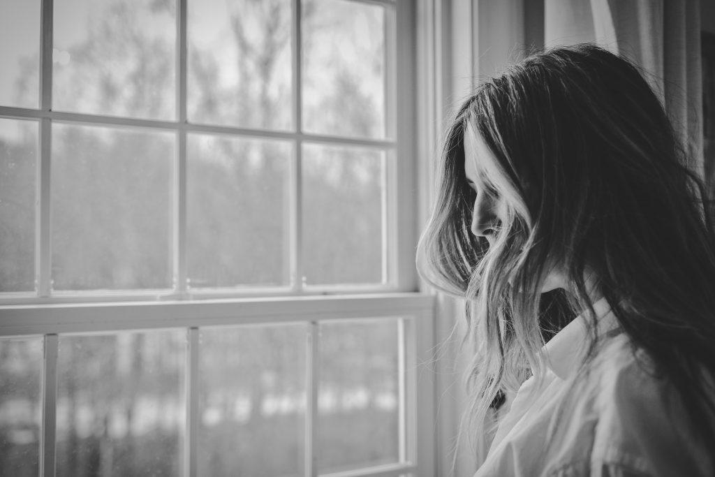 Femme regardant la fenêtre depuis son domicile.