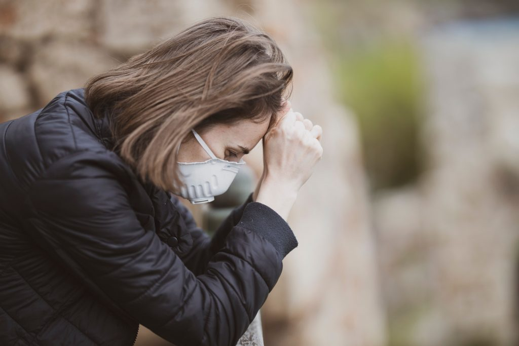 Femme portant un masque chirurgical se tenant la tête entre ses mains.