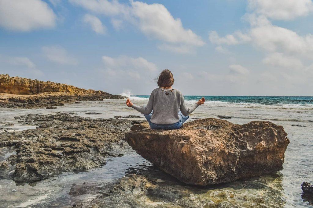 personne faisant de la méditation sur un rocher en bord de mer